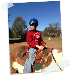 Braden on horseback with a wide smile on his face.